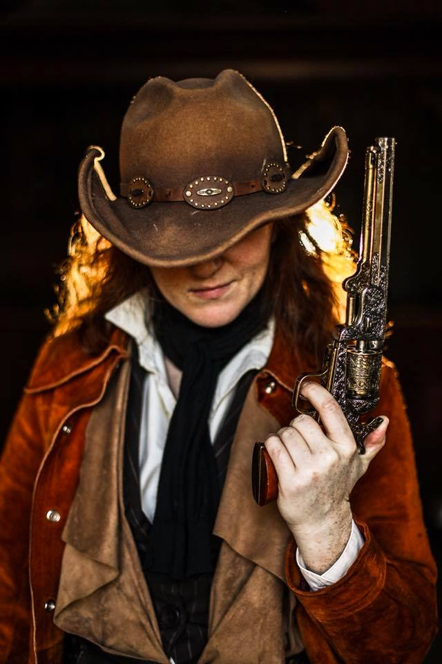 Adrianna in a cowgirl costume holding an 1851 colt revolver
