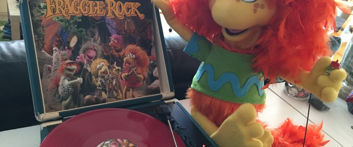 Fraggle puppet with orange hair sits beside a Fraggle Rock vinyl record and record player